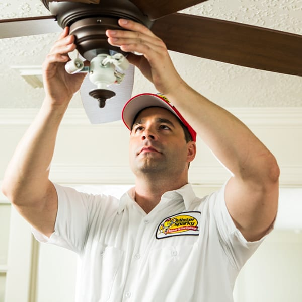 A Mister Sparky Kansas City electrician installs a ceiling fan.